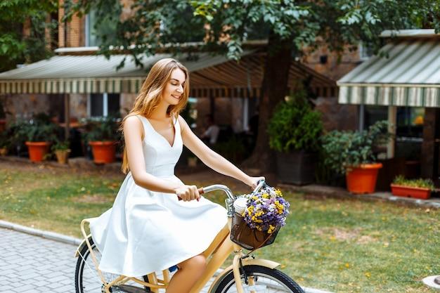 Девушка едет по улице на велосипеде