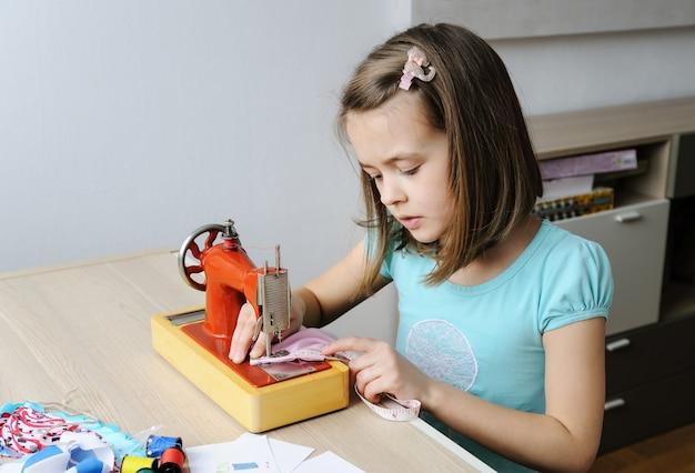 女の子はミシンで人形のドレスを縫っています。彼女は製品を測定するために巻尺を使用しています。