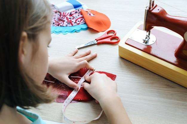 女の子は人形のドレスを縫っています。彼女は製品を測定するために巻尺を使用しています。