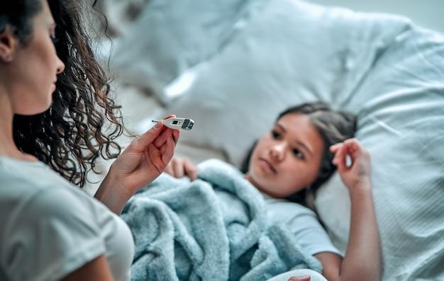 소녀가 아파요. 엄마는 온도계를 사용하여 온도를 측정합니다.