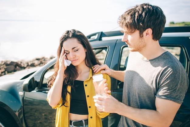 その少女は病気か泣いている。彼女のボーイフレンドは彼女を助けたいと思っています。車での家族旅行中に若い女性が病気になった。
