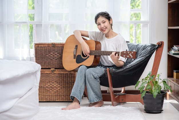 女の子は椅子に座ってギターを弾いています。