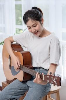 Девушка сидит и играет на гитаре на стуле.