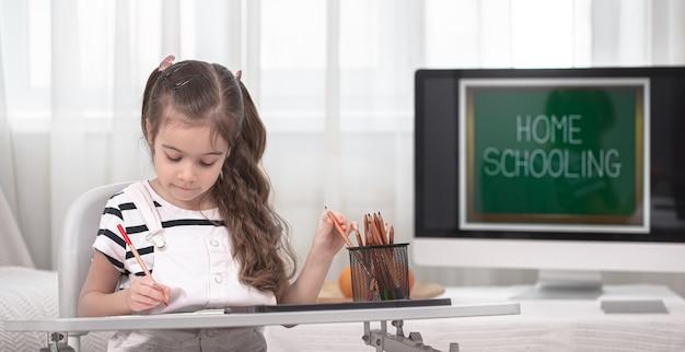 소녀는 테이블에 앉아 숙제를하고 있습니다. 아이는 집에서 배웁니다. 홈 스쿨링 및 교육