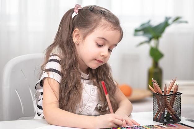 소녀는 테이블에 앉아 숙제를하고 있습니다. 아이는 집에서 배웁니다. 홈 스쿨링 개념.