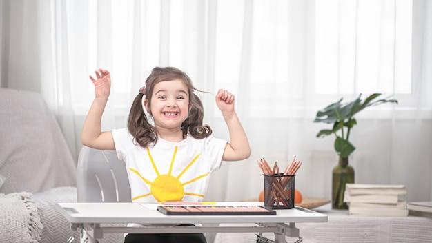女の子はテーブルに座って宿題をしています。子供は家で学びます。ホームスクーリング。テキストのためのスペース。