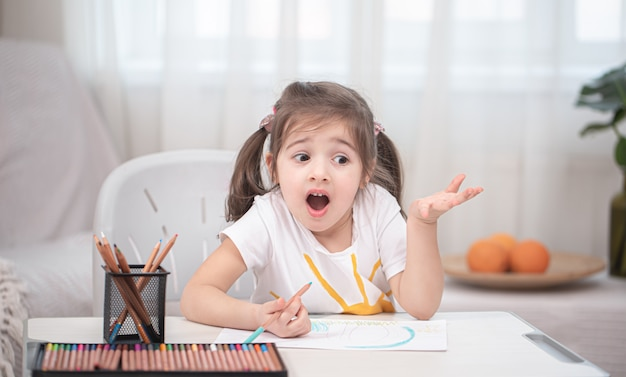 女の子はテーブルに座って宿題をしています。