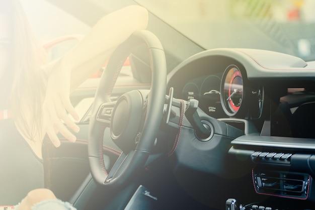 소녀는 자동차의 바퀴 뒤에 앉아 있습니다. 현대 자동차의 검은 가죽 인테리어.