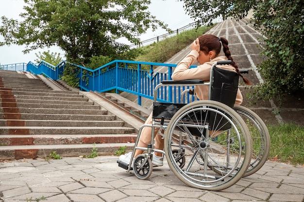 少女は一人で困難に直面し、落ち込んで車椅子に座っています。車椅子、障害者、フルライフ、麻痺、障害者、ヘルスケアの概念。
