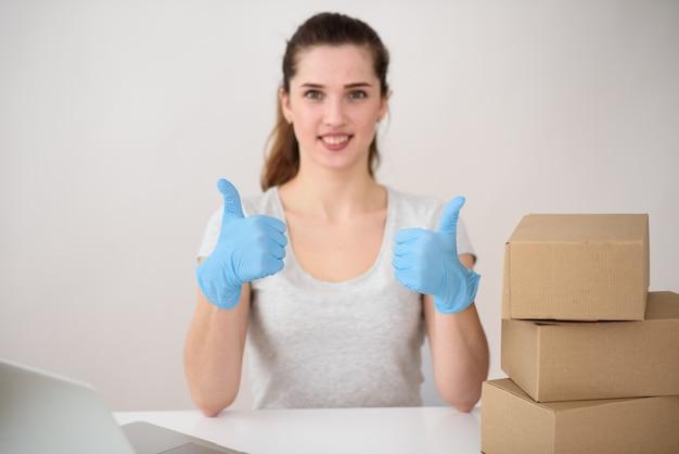少女は親指を立てたテーブルで服を着たゴム手袋に座っており、箱が近くにあります。非接触型配送のコンセプト