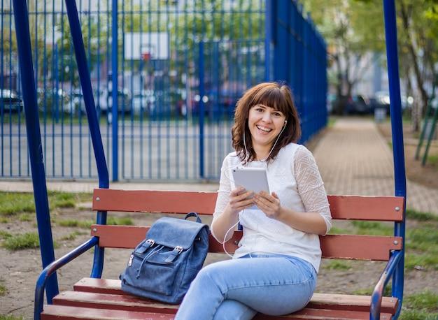 Девушка сидит на скамейке с планшетом и смеется. брюнетка в белом пиджаке и джинсах на улице