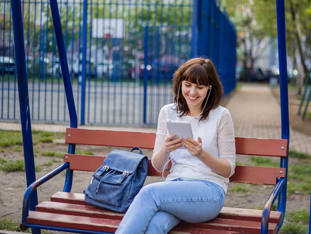 Девушка сидит на скамейке с планшетом и смеется. дистанционное общение в карантине. брюнетка в белом пиджаке и джинсах на улице