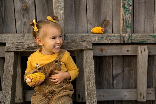 그 소녀는 옥수수를 손에 들고 오래된 나무 계단에 앉아 있다