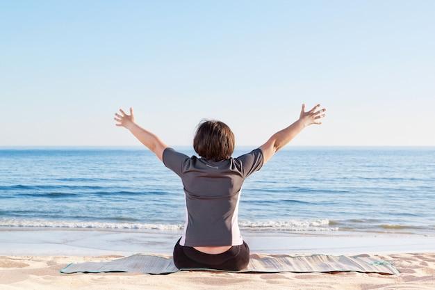 Девушка сидит на пляже и приветствует мир и счастье. летом море.