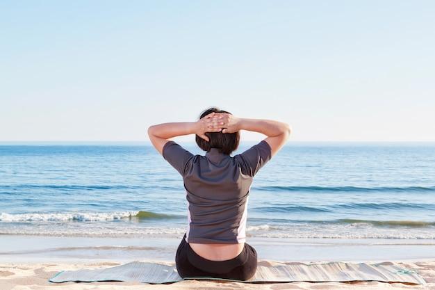 Девушка сидит на пляже, занимаясь йогой. летом море.