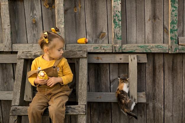 그 소녀는 계단에 앉아서 겁에 질린 고양이를 보고 있다