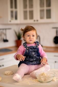 女の子はテーブルに座って、彼女の顔と服は小麦粉で汚れています
