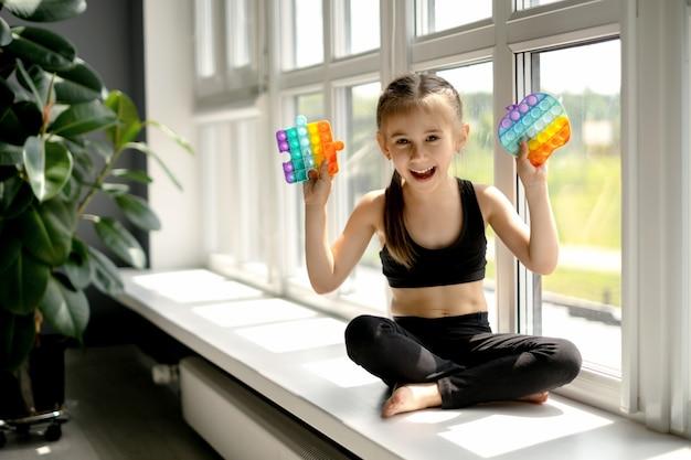 Девушка сидит на подоконнике у большого окна и играет с игрушкой pop it.