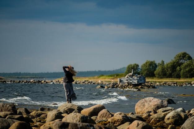少女は白海の岸にドレスを着て立っています。