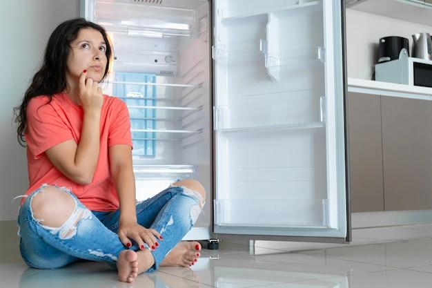 소녀는 빈 냉장고에 놀란다. 식량 부족. 음식 배달.