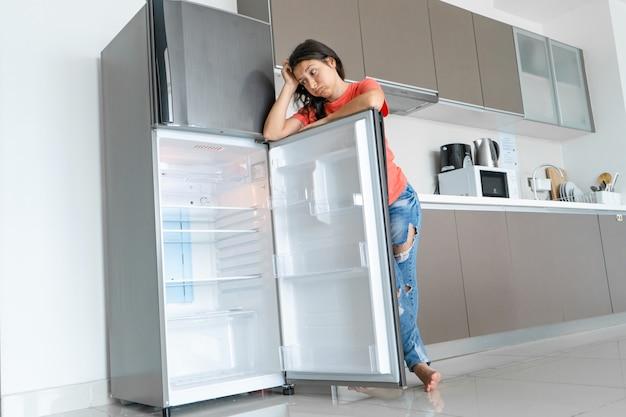 女の子は空の冷蔵庫に驚いています。食糧不足。食品の配達。