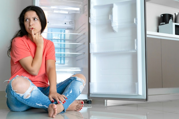 Девушка удивляется пустому холодильнику. недостаток еды. доставка еды.
