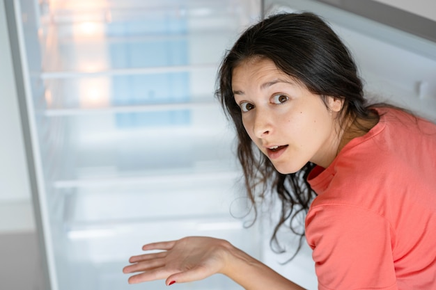 女の子は空の冷蔵庫に驚いています。食糧不足。食品デリバリー。