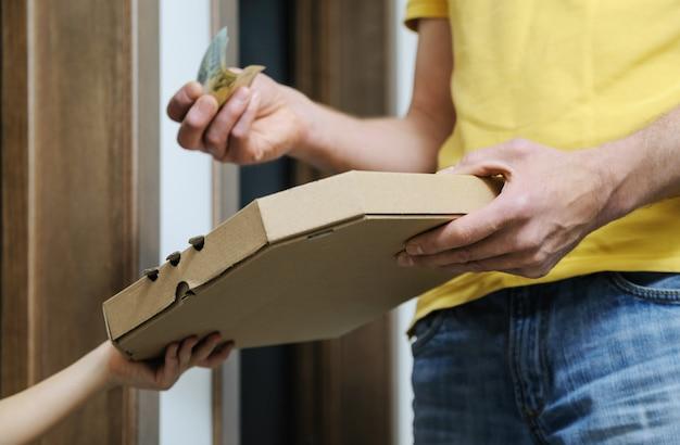 女の子はピザの配達人から箱を取っています。