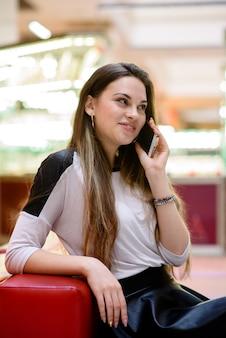 Девушка разговаривает по телефону в торговом центре
