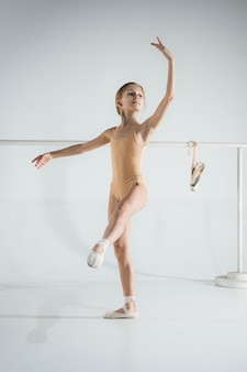 女の子はバレエバレの近くでトレーニングをしています。