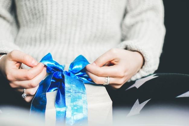 소녀는 선물에 활을 매고 있습니다. 선물 포장. 블루 나비 선물. 공예 종이 선물