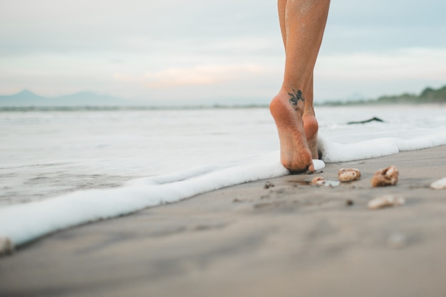 女の子はビーチに沿って歩いている