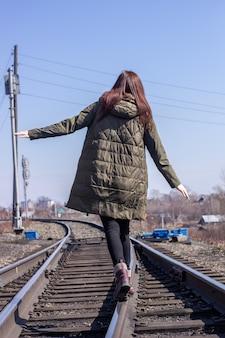 소녀는 앞에 철도를 걷고있다