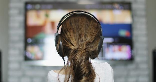 女の子はスマートテレビを見ています焦点は女の子にあり、テレビはぼやけています