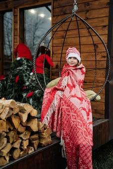 女の子は赤い毛布に包まれて、ぶら下がっているブランコに座っています