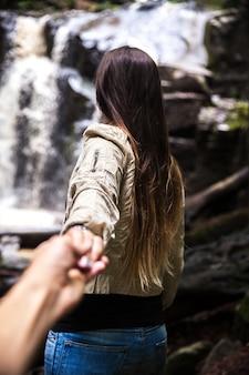 Девушка ведет своего парня к красивому водопаду. природа