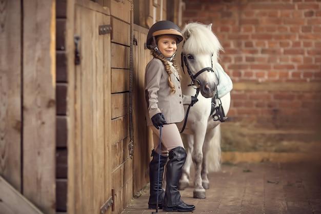 女の子は馬小屋から彼女のポニーを導きます