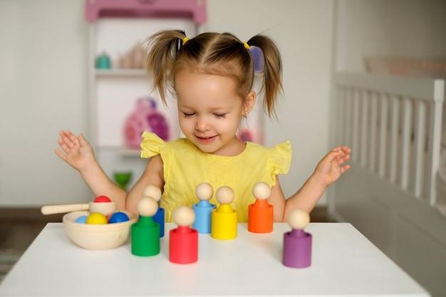 Девочка учится краскам, играя с деревянными цилиндрическими игрушечными раскрашенными фигурками.