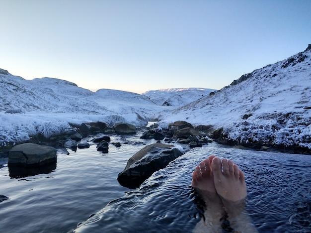 女の子は雪山の素晴らしい景色と屋外の温泉に横たわっています。冬の素晴らしいアイスランド