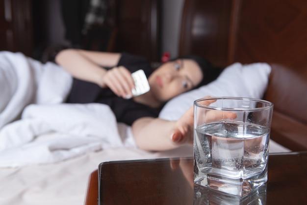 Девушка лежит в постели и хочет принять лекарство