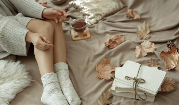 女の子は暖かい靴下、秋の気分、快適さでお茶を飲みながらベッドに横たわっています。