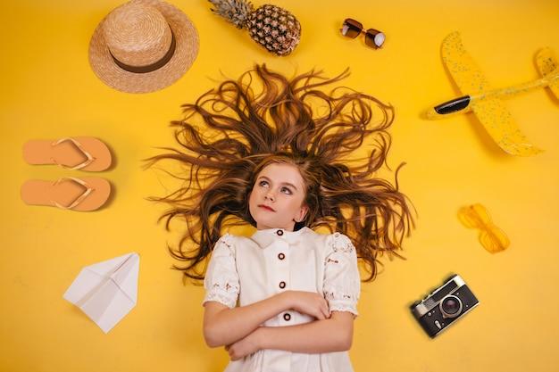 女の子は黄色の背景にあり、彼女の周りにはスリッパ、パイナップル、帽子、飛行機、カメラがあります