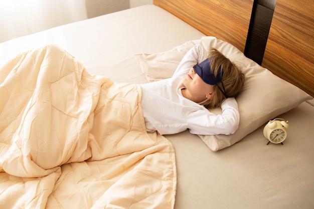 少女は朝、目と笑顔のマスクでベッドに横になり、窓からおはようの日差しが降り注ぐ。