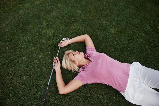 여자 아이는 골프장에 누워 경기 후 이완합니다