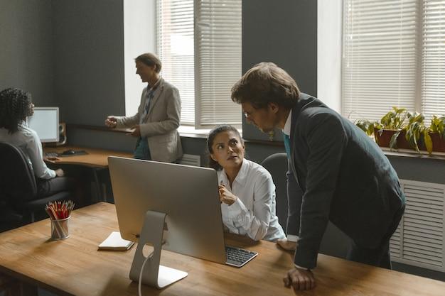 Девушка слушает своего руководителя, который дает новые настройки. сотрудники много работают в команде, чтобы