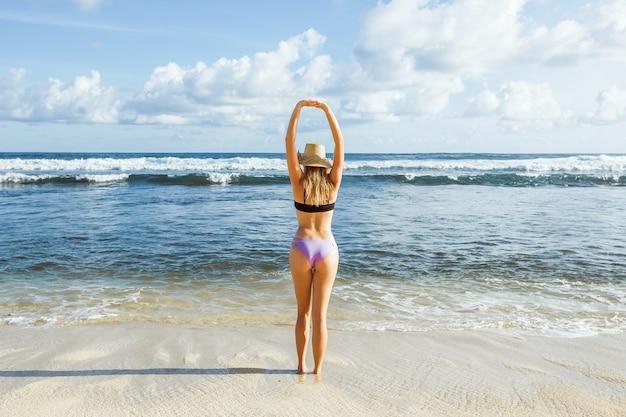 Девушка смотрит на океан и тянется вверх, вид сзади
