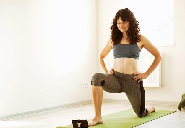 Девушка смотрит в телефон и тренируется дома - молодая женщина прыгает на спортивный коврик -