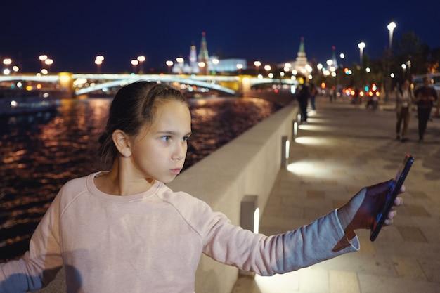 女の子は夕方のライトの背景にあるウォーターフロントのスマートフォンをのぞき込みます。