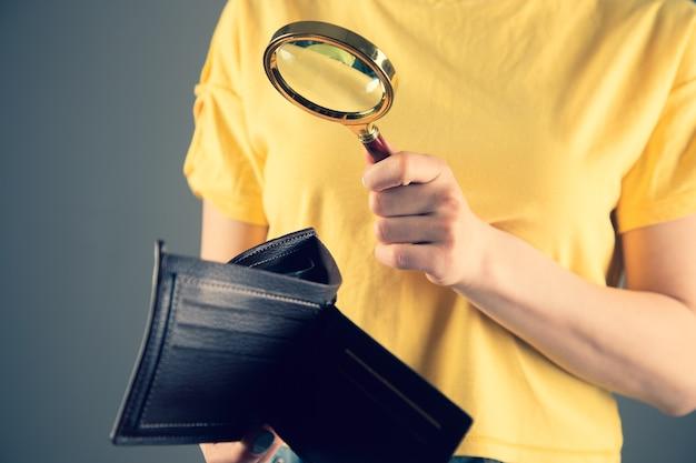 Девушка смотрит в бумажник через лупу. концепция изучения баланса