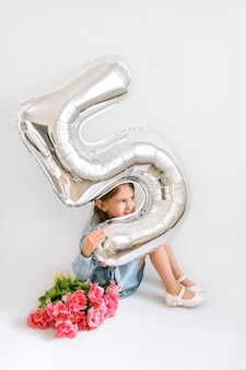 Девушка улыбается из-за большого воздушного шара в виде цифры пять.